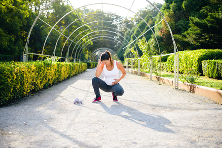 Sporty femme enceinte se sentir le nez du bébé lors d & # 39 ; un entraînement de remise en forme saine dans le parc Banque d'images - 91043643