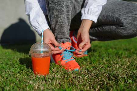 Sinaasappel en wortel detox smoothie. Sluit omhoog van vrouw die sportschoenen rijgen voor het worden klaar voor fitness training. Gezonde levensstijl concept.