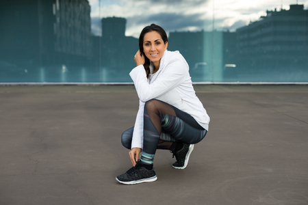 Female athlete lacing running shoes. Cheerful sporty woman on urban fitness workout. Runner ready for training. Banque d'images - 94124288