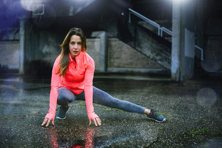 Motivated female athlete stretching legs for warming up before urban fitness and running workout under the rain at night. Sporty woman exercising outside in the city while it is raining. Stock fotó