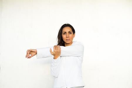 Sporty woman doing fitness stretching exercise for arm and shoulder.