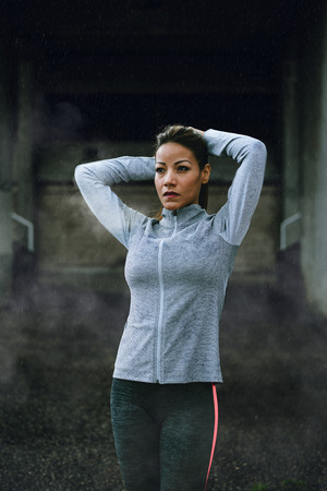Motivated woman getting ready for outdoor winter fitness workout under the rain. Latin athlete exercising on cold and raining day.