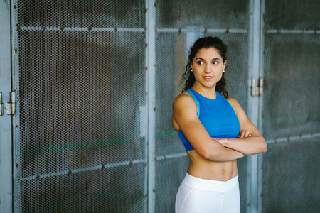 Confident young fit female athlete crossing arms. Sportswoman posing outside. Workout success and healthy lifestyle concept. Stock Photo