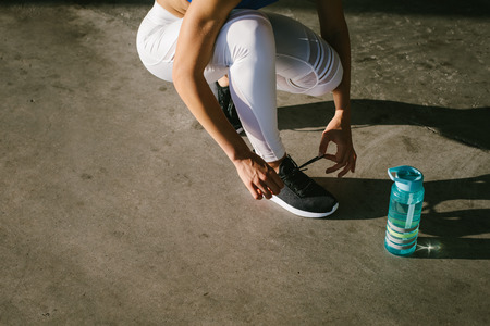 Close up of female athlete lacing footwear and getting ready for urban running and fitness workout. Healthy lifestyle concept.