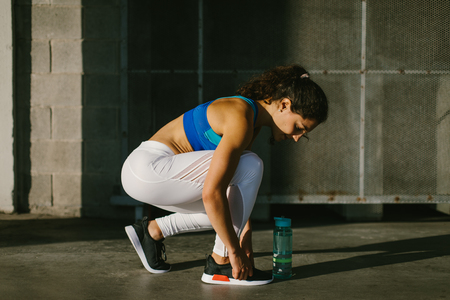 Young sporty female athlete lacing footwear and getting ready for urban running and fitness workout. Motivated woman training outside.