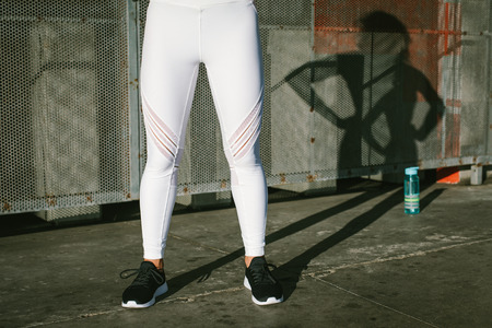 Close up of female athlete legs wearing white fitness leggings. Healthy lifestyle and workout concept. 写真素材