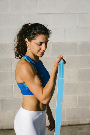 Fitness young woman doing biceps curl with resistance band for training arms strength. Female athete exercising outside.
