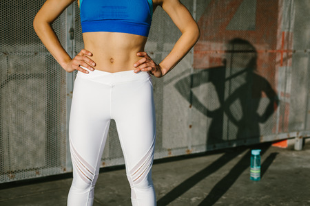 Fitness urban workout concept. Close up of fit sporty woman legs and torso.