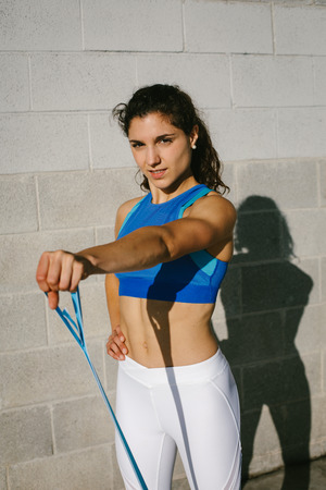 Fitness young woman doing front raises with resistance band for training shoulders strength. Female athete exercising outside.