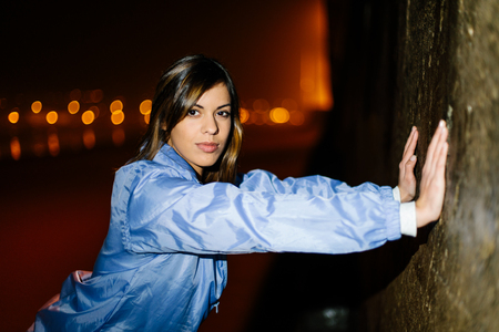 Young fitness woman training and exercising at night on a city beach. Female athlete doing wall push-ups.