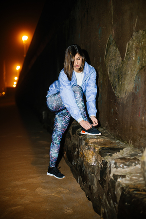 Young fitness woman lacing footwear for getting ready before night workout  at city beach. Female athlete doing wall push-ups. Stockfoto