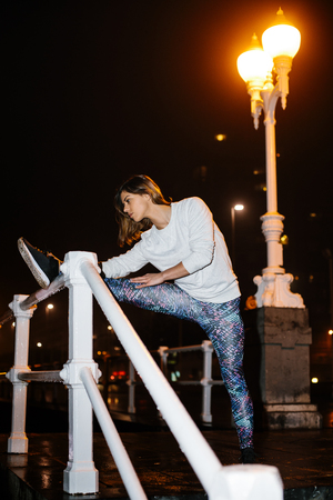 Female athlete stretching for warming up before running at night in the city. Fitness urban workout.
