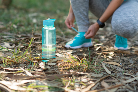 Sporty woman taking a workout rest for lacing sport shoes during outdoor nature workout. Focus on fitness bottle on water in the foregroung. Healthy exercising concept.
