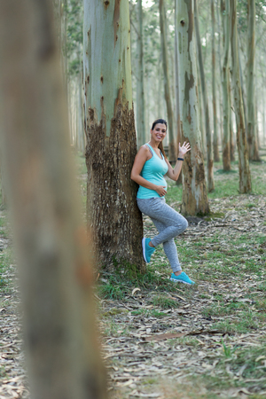 Sporty pregnant woman waving. Female athlete taking a rest during outdoor healthy fitness workout in nature. Expectant healthy mother taking a break.