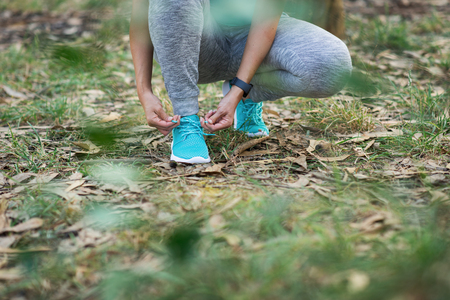 Sporty woman getting ready for fitness outdoor workout in nature. Female athlete lacing sport footwear. Healthy exercising concept.