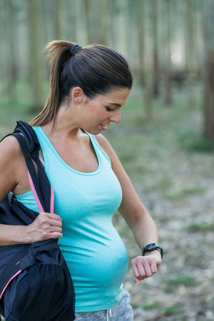 Sporty pregnant woman feeling a contraction during outdoor workout. Female athlete checking the time.