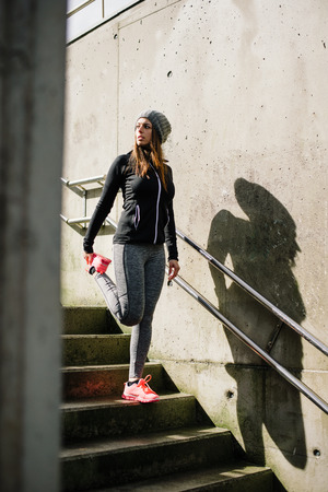 Sporty urban woman stretching and warming up legs before running in the city. Sport and healthy lifestyle concept.