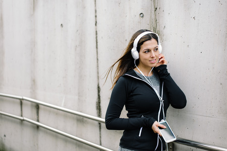Urban fitness woman taking a workout rest for relaxing and listening music with headphones. 写真素材