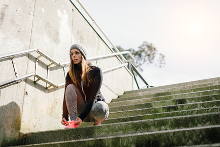 Motivated female athlete getting ready for urban morning running workout. Banque d'images - 99911977
