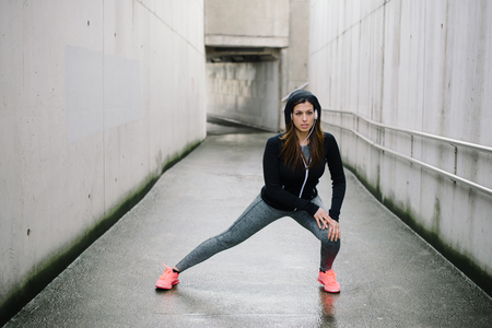 Sporty woman stretching and warming up legs for running urban fitness workout. Sport and healthy lifestyle concept. Female athlete exercising outside. Stock Photo