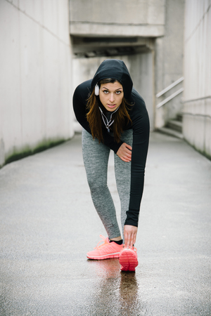 Sporty woman stretching and warming up legs before running urban fitness workout. Sport and healthy lifestyle concept. Female athlete exercising outside. Stock Photo