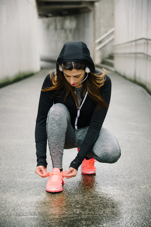 Motivated sporty woman getting ready for urban running workout.