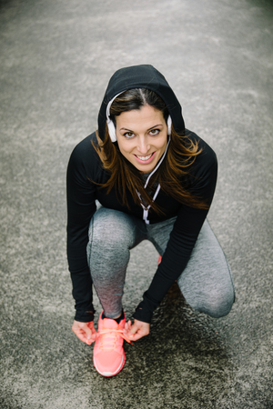 Motivated female athlete getting ready for urban morning running workout. Stockfoto