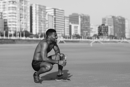 Motivated black man taking a workout rest for drinking water. Runner resting after running at city beach. Banque d'images - 100360708