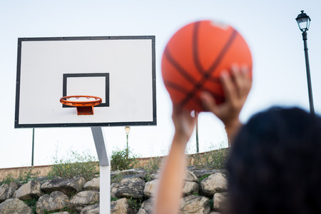 Detail of female hands throwing the ball to the hoop. Basketball play concept. Stock Photo