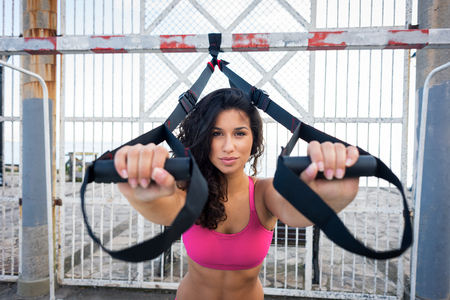 Fitness workout motivation. Sporty woman training with trx straps.