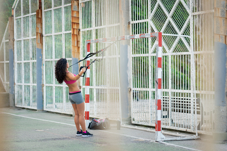 Woman training back and shoulders with trx straps. Rear delt fly fitness exercises.