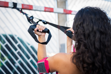 Woman training biceps with trx straps. Fitness suspension urban workout.