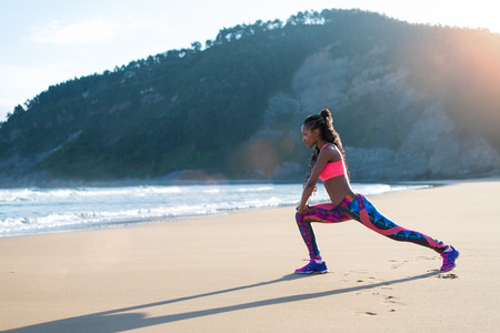 Fitness woman stretching legs or doing lunges at the beach. Black Female athlete doing relaxing exercise towards the sea. Reklamní fotografie - 101376628