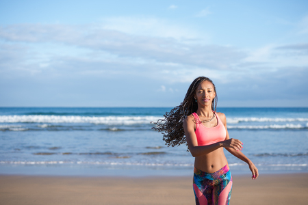 Sporty woman with dreadlocks running at the beach against the sea. Fitness summer lifestyle.
