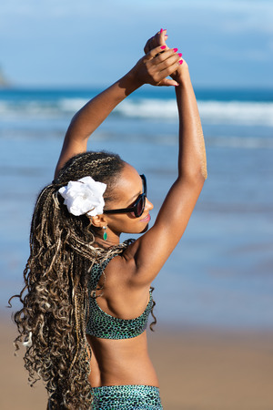 Young black woman with summer braids enjoying and relaxing on vacation at the beach. Female in fashionable ethnic bikini.