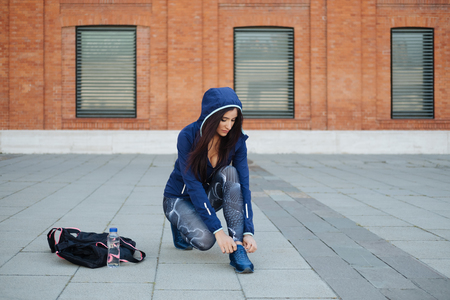 Stylish sporty young woman lacing footwear and getting ready for urban workout. Fitness motivation concept.