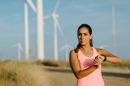 Female motivated athlete using sport watch for timing running training.