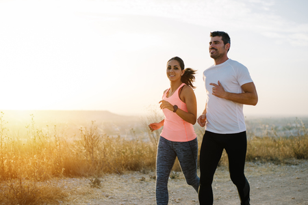 Two athletes running at sunset. Man and woman training together. Stockfoto