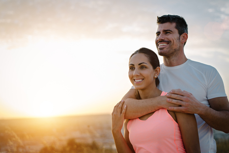Couple healthy and fitness lifestyle. Happy sporty lovers portrait during outdoor training at sunset. Stock Photo