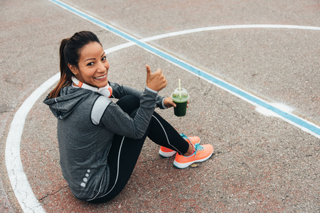 Successful fitness woman drinking detox green smoothie during outdoor urban workout rest. Sport nutrition and healthy lifestyle concept. Female athlete taking a break sitting on the ground.