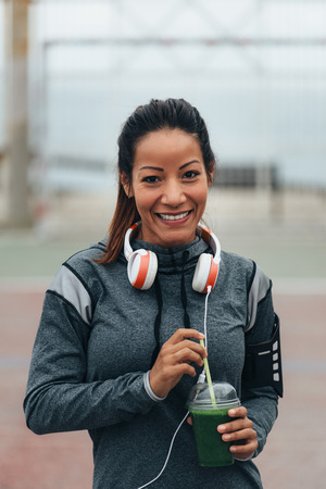 Young fitness woman drinking detox green smoothie during outdoor city workout rest. Sport nutrition and healthy lifestyle concept.
