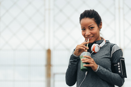 Happy fitness woman drinking detox green smoothie during outdoor city workout rest. Sport nutrition and healthy lifestyle concept. Stock Photo