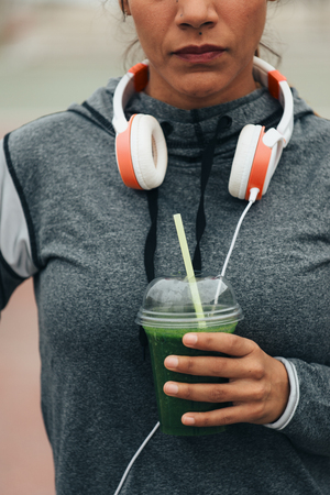 Healthy sport and fitness nutrition concept. Woman drinking green detox smoothie during workout rest.