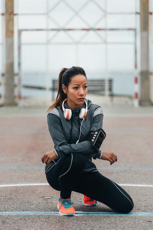 Atleta urbano femminile che riposa durante l'allenamento all'aperto. Stile di vita fitness e concetto di esercizio. Donna sportiva che prende una pausa di formazione.