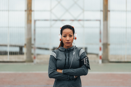 Empowered and confident sporty woman portrait. Female athlete on urban workout wearin headphones. Stock Photo