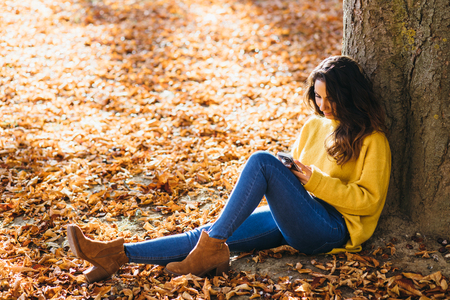 Casual young woman using her smart phone and sitting outdoor in autumn.