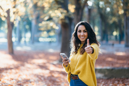 Cheerful woman using smartphone and doing success thumbs up gesture in autumn at city park.