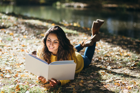 Happy casual woman reading a book at river shore in autumn.
