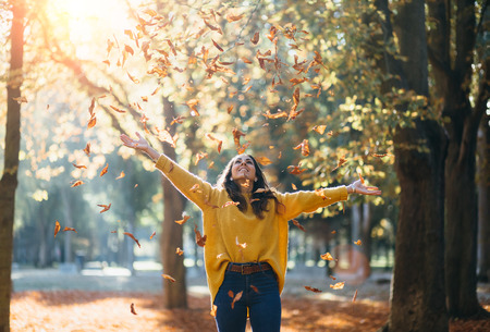 Casual joyful woman having fun throwing leaves in autumn at city park. Reklamní fotografie - 104976085