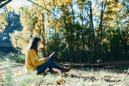 Casual woman reading a book at river shore in autumn.